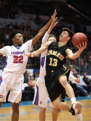 McQuaid's Josh Purcell (13) drives to the basket against Fairport's Vanzell Johnson (22) in the Class AA semifinal game.