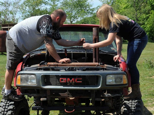Cierra Andrews and her father, Louie, work on the carburetor on one of the mud bog trucks after it stopped working May 23 at their home on Chillicothe-Lancaster Road. Last-minute fixes are common before mud bog events.