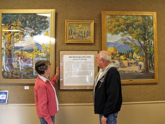 Tularosa Basin Museum docent Donna Doyle Milburn and Alamogordo historian and retired educator Dr. Dave Townsend observe original paintings belonging to Alamogordo at Patron's Hall Wednesday.