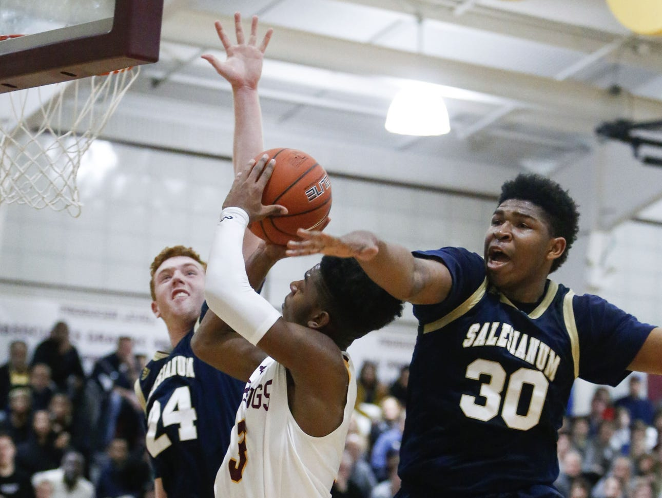 St. Elizabeth's Elijah Dockery tries to get to the basket between Salesianum's Paul Brown (left) and Tariq Ingraham in the second half of the Vikings' win at the St. E Center Friday.