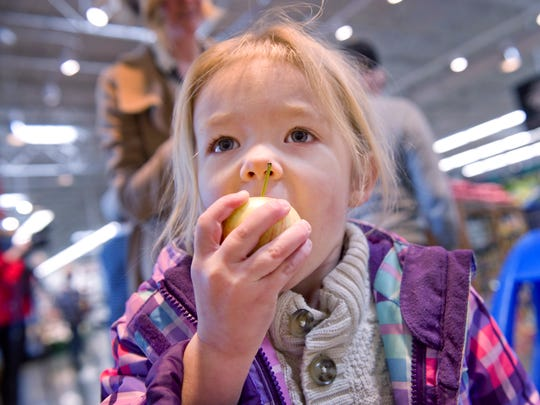 Julep Peach, 3, munches on an apple during the grand opening of the new Schnucks supermarket at Lawndale Commons Wednesday morning. The store offers free fruit to kids 10 years or younger when accompanied by a parent. Her mom, Allie Peach, served her other daughter, Charlie, 1, a banana.
