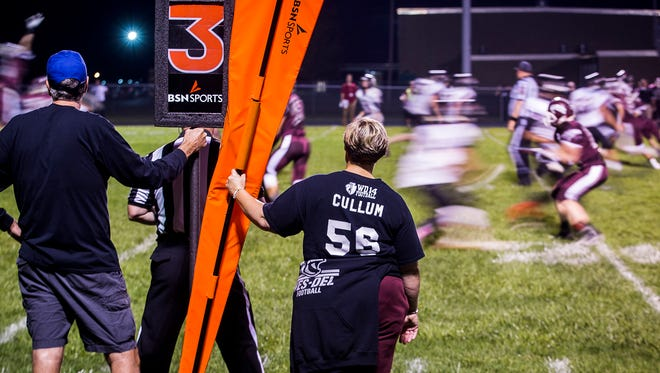 Amy Cullum, a Wes-Del High School teacher and the mother of Alex Cullum, volunteers on the chain gang during Wes-Del's game against Edinburgh.