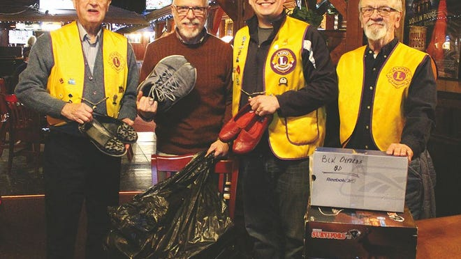 Pratt Lions Club members (from left, in yellow vests) Denis Rasmussen, Andy Lee and Garey West, contribute new and gently-used shoes gathered by Lions members to Kiwanis representative Ron Moser (second from left) at their club meeting in the first week of February. The Kiwanians will be gathering shoes through March at several places in Pratt, for donation to third-world countries.