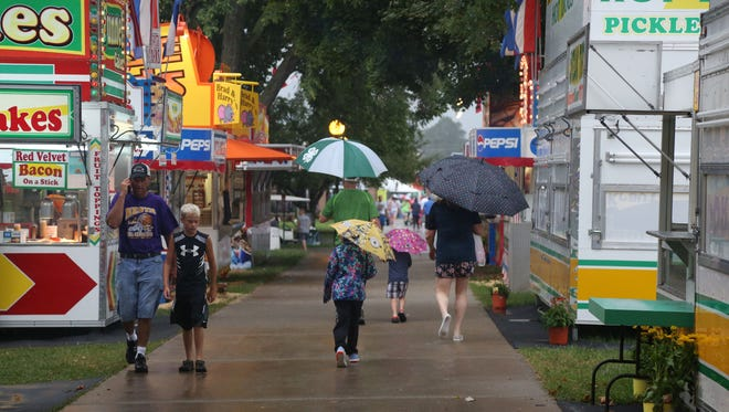 People brave the rain on the morning of the first day of the Iowa State Fair on Thursday, Aug. 11, 2016, in Des Moines. A brief rain storm hit the fair but cleared off by late morning.