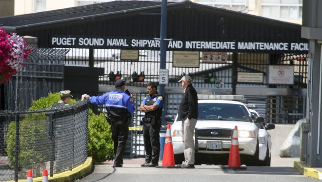 Police stand by outside the main gate of Puget Sound Naval Shipyard, where a suspicious package was discovered shortly before noon Thursday. Shipyard and Naval Base Kitsap-Bremerton personnel sheltered in place, and downtown Bremerton streets were blocked, while the package was investigated.