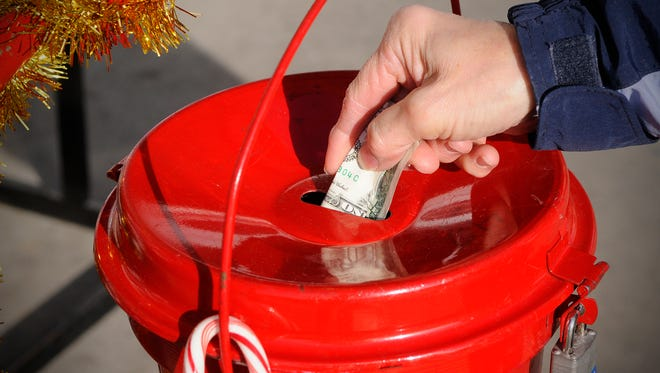 A donation is made to a Salvation Army red kettle.