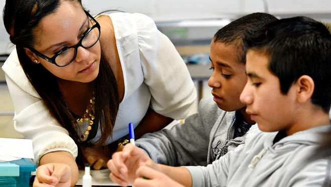 In this file photo, bilingual English Language Learners (ELL) Aid Marianela Rosario, left, a former student and William Penn High School graduate, works with students Junior Severino, 15, center, and Kevin Ramos, 15, right, at William Penn High School in York, Pa., on Tuesday, Nov. 17, 2015. (Dawn J. Sagert - dsagert@yorkdispatch.com)
