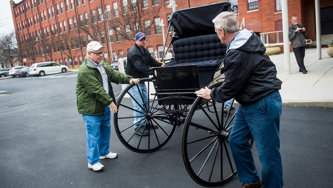 Former fire commissioner James Roth and firefighter Brian McDermitt along with members of the Hanover Area Historical Society move an 1889 courting buggy from the Hanover Fire Museum to the Carriage House at Warehime-Myers mansion on Nov. 18, 2015.
