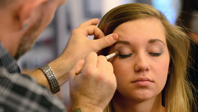 Christopher Endsley, a colorist at Douglas J Salon and Day Spa, applies eye shadow on Karleigh Madaj in October 2015. Douglas J is accepting transfer students from Regency Beauty Institute, which closed Thursday.