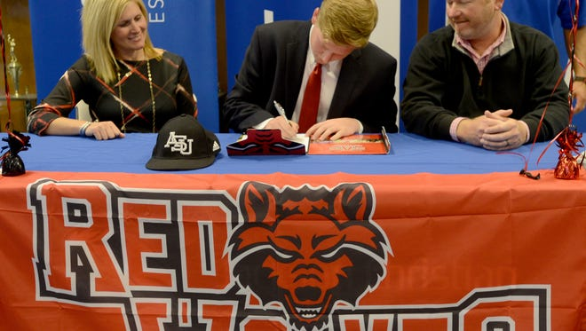 Jackson Christian senior baseball player Carter Holt is joined with his parents, Luanne and Brent Holt, as he signs his letter of intent to Arkansas State, Wednesday afternoon.