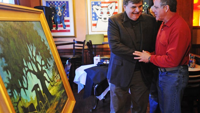 """George Rodrigue, left, talks with David Begnaud, one of many supporters on hand for the unveiling of Rodrique's latest painting the """"Youngsville Heritage Oak,"""" Tuesday, Feb. 8, 2011, at the Blue Dog Cafe in Lafayette. Profits from screen prints sold of the painting will be used, in partnership with Guardian of the Oaks, to save the 250 year old oak tree in Youngsville. The tree is scheduled to be cut down to make way for a temporary road while a roundabout is built.(Photo by Denny Culbert/ dculbert@theadvertiser.com)"""