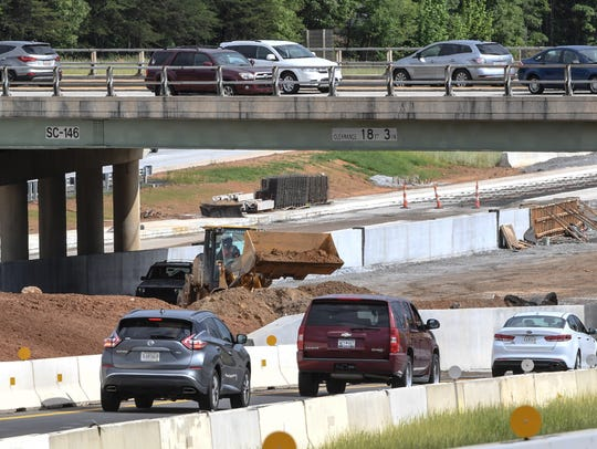 Cars drive on Woodruff Road, bridge over construction