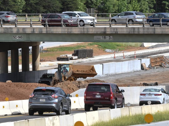 Cars drive on Woodruff Road, bridge over construction along state highway 385 in Greenville on Wednesday. Construction projects on both roads, and nearby I-85 have created traffic slow downs.