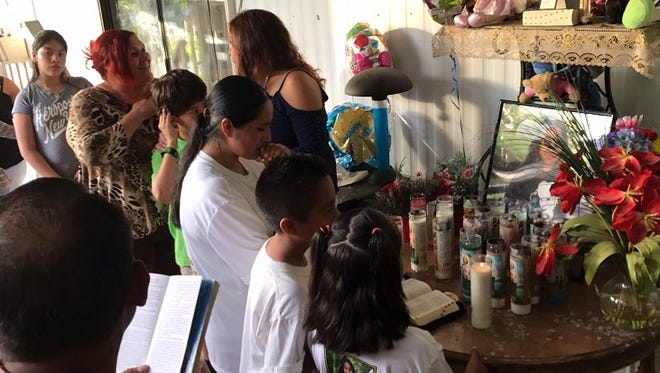 Rita Hernandez, center in white, prays for her daughter Diana Alvarez, with friends and family at the San Carlos Park trailer where she disappeared a year ago.