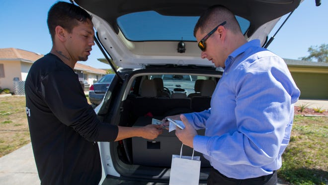 Cape Coral resident Stephen Hunt, 35, pays for his medical marijuana vaporizer pen after delivery to his home by Matthew Lipani, an assistant manager with Surterra.