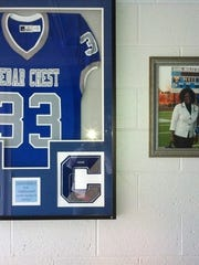 The Cedar Crest Falcon football jersey worn by Charles Kyeremeh Jr. and photos of him with his parents hang on the wall of the family's home in North Cornwall Township.