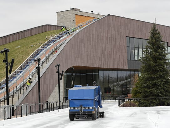 The Zamboni resurfaces the ice rink as workers construct the side barrier on the sledding hill in the Titletown District on Tuesday, November 21, 2017 in Ashwaubenon, Wis.