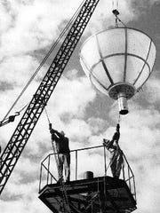 """Workers install the """"Blue Flame"""" atop the El Paso Natural"""