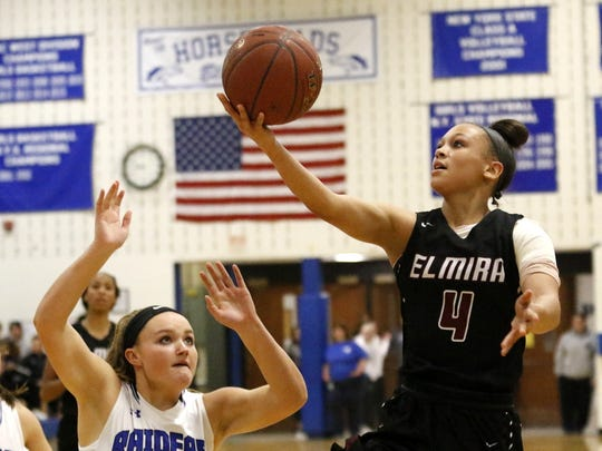 Kiara Fisher of Elmira goes in for a layup in front of Marissa Adams of Horseheads on Tuesday during the Express' 67-43 win at Horseheads Middle School.