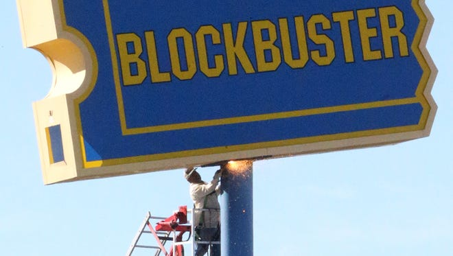 Workers prepare to remove a sign to the former Blockbuster video rental Westside location at 6135 N. Mesa on Tuesday morning. El Paso's four remaining Blockbuster locations closed in late March due to declining sales and expiring location leases. The stores stayed open for several weeks to sell their stock of DVDs and games.