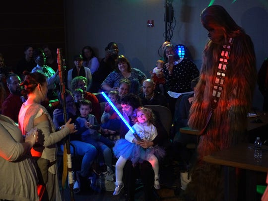 Deanna Pedicone, a Delaware Department of Health and Social Services worker, holds her 4-year-old daughter Zoe in her lap while she takes in all the Star Wars characters that attended her official adoption at the New Castle County Courthouse on Friday.