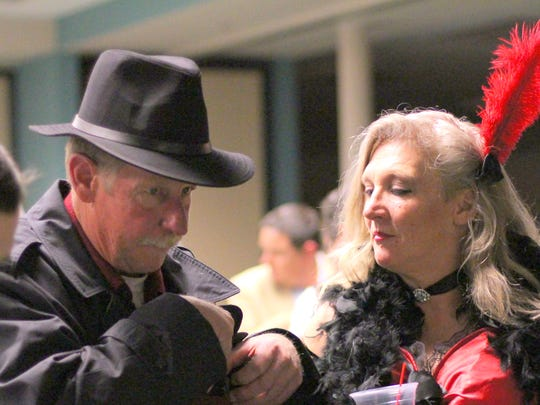 Brian Davey, left, reaches in his pocket for some chip money as Kaylinda Midgette waits to join in a game of Black Jack during Saturday's 101st Chamber Gala.