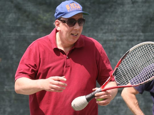 Dr. Don Mueller demonstrates how he uses a racquet