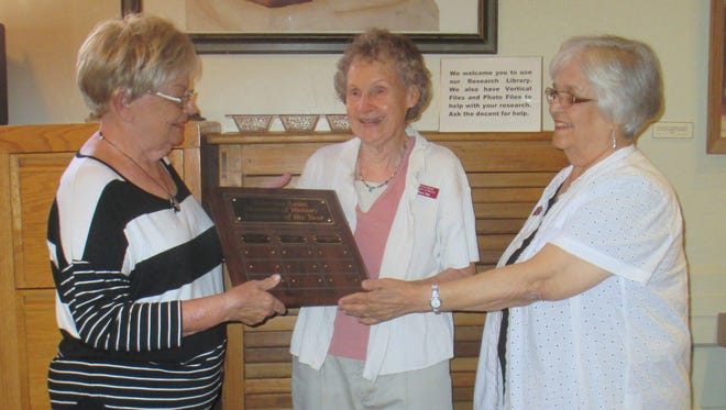 Josette Herrell (L) and Alice Baxter (R) show Mary Pat Jones (C) the Tularosa Basin Historical Society's Volunteer of the Year plaque one last time before hanging on the Tularosa Basin Museum of History's wall.