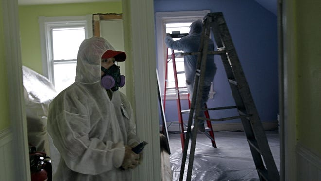 Contractors clean up lead paint in a contaminated building. Research has shown that children could suffer harm from concentrations of lead lower than the old standard, Centers for Disease Control and Prevention officials said.