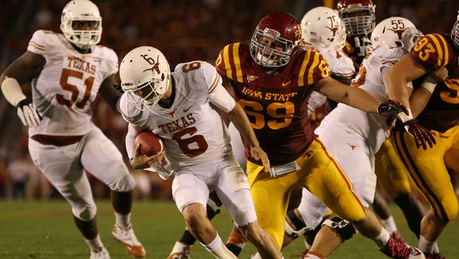 Iowa State defensive lineman Nick Kron (69) chases down Texas quarterback Case McCoy during an NCAA college football game between Iowa State and Texas at Jack Trice Stadium in Ames, Iowa on Thursday, Oct. 3, 2013.