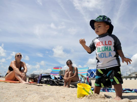 Logan Eng, 2, right, plays with sand as his mom, Avia Eng, center, of Howell, N.J., and their friend Jenny Caruso, left, of Red Bank, N.J., look on during a beach outing, Friday, July 20, 2018, in Long Branch, N.J.