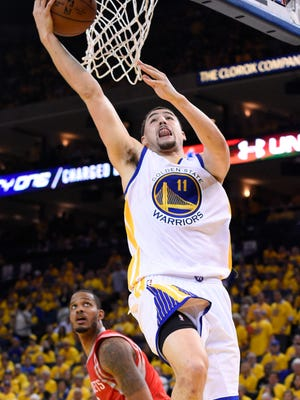 Golden State Warriors guard Klay Thompson (11) shoots in front of Houston Rockets forward Trevor Ariza (1) during the third quarter in game five of the Western Conference Finals of the NBA Playoffs at Oracle Arena.