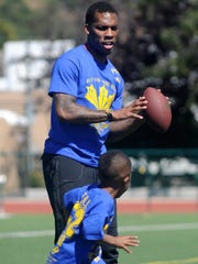 Troy Hill helps youths learn receiver routes during Hill's Defying Your Odds youth football camp at St. Bonaventure High on April 16 in Ventura.