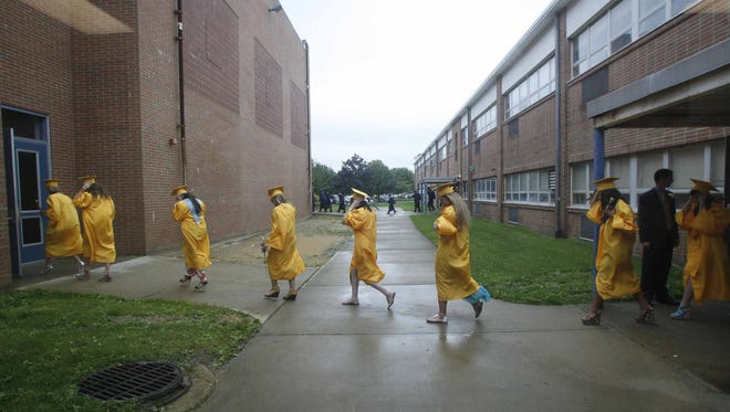 Graduates from Toms River High School North walk to the Pine Belt Arena next door on a wet and windy commencement day in  June 2012.