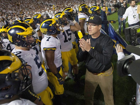 Jim Harbaugh talks with his team before action against Penn State on Oct. 21, 2017 at Beaver Stadium in University Park, Pa.