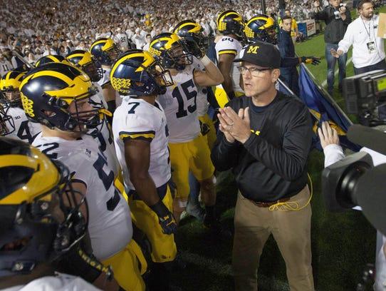 Michigan head coach Jim Harbaugh talks with his team