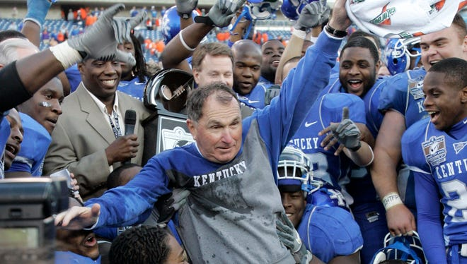 Kentucky coach Rich Brooks jumps into a group of his players as they are awarded the championship trophy after defeating Clemson 28-20 in the Music City Bowl college football game in Nashville, Tenn., Friday, Dec. 29, 2006.