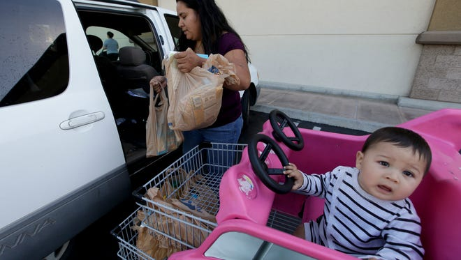Irma Salazar, left, of Santa Ana, Calif., loads plastic grocery bags into her car as her son Miguel looks on Tuesday. Gov. Jerry Brown signed into law Tuesday the nation's first statewide ban on single-use plastic bags.