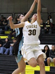 Faith Silva attempts a lay-up while being heavily guarded by a Santa Teresa player.