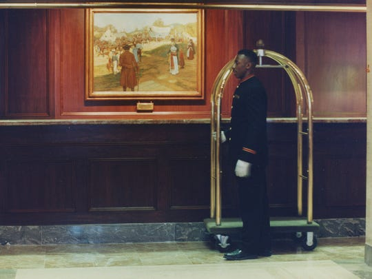 """Bellman Steven Outlaw walks by Howard Pyle's """"Conestoga Powder Wagon"""" hanging in the lobby of the Hotel du Pont."""