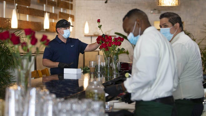 Dustin Parfitt, chef and owner of Oli's Fashion Cuisine in Wellington trims roses leftover from Mother's Day for decorating tables at the restaurant, May 11, 2020. Oli's reopened Monday, with added space between tables inside and outside. Parfitt used the time that the inside dining was closed due to the coronavirus outbreak to repaint and and spruce up the interior. Parfitt said they will continue to sell produce and sanitizing supplies.