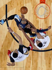 Memphis Grizzlies guard Mike Conley (11) goes to the basket against New Orleans Pelicans forward Anthony Davis and center Alexis Ajinca (42) in the second half of an NBA basketball game in New Orleans, Tuesday, March 21, 2017. The Pelicans won 95-82. (AP Photo/Gerald Herbert)