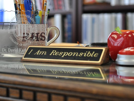 Karl Carpenter, principal of Pineville High School for nine years, keeps this reminder on his desk. He is a proponent of strong leadership and talked about that in an essay as finalist for Principal of the Year.