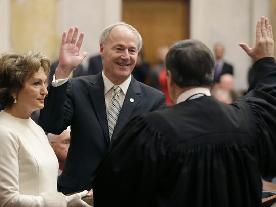Gov. Asa Hutchinson, center, takes the oath of office from Arkansas Supreme Court Chief Justice Jim Hannah, right, as his wife, Susan, watches at the Arkansas state Capitol in Little Rock on Tuesday.