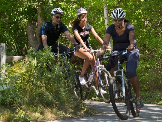 President Barack Obama, left, bike rides with daughter Malia Obama and first lady Michelle Obama, Friday, Aug. 15, 2014, on the Manuel F. Correllus State Forest bike path outside of West Tisbury, Mass., during the Obama family vacation on the island of Martha's Vineyard.