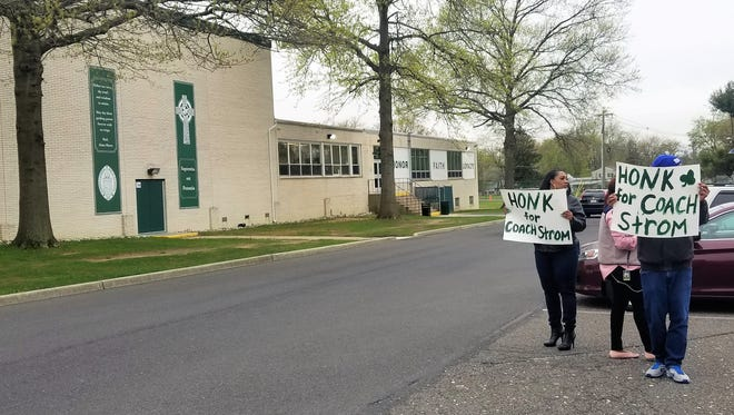 Supporters hold up signs for Nick Strom on Monday morning at Camden Catholic High School. Strom, a history teacher, football and golf coach at the school, was notified Friday his contract will not be renewed as a teacher.