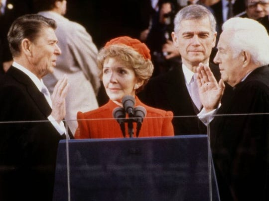 President Ronald Reagan being sworn in January 20, 1981 by Chief Justice of the Supreme Court, Warren Burger, Mrs. Reagan stands in the center.