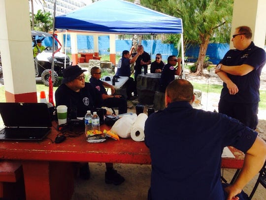 Local and military rescuers gather at the command post at Matapang Beach on Monday, Aug. 10, to continue searching for a missing swimmer.