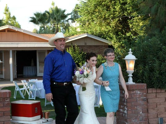 Taryn Garrod is escorted down the aisle during her