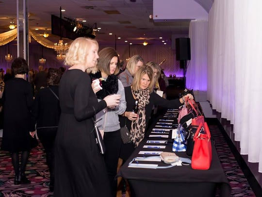 Guests browse silent auction purses at the 2018 Handbags